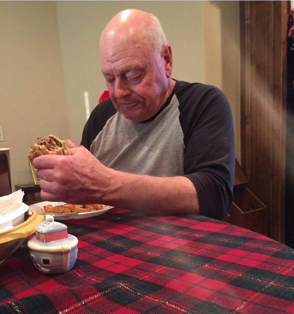 papaw eating a hamburger alone